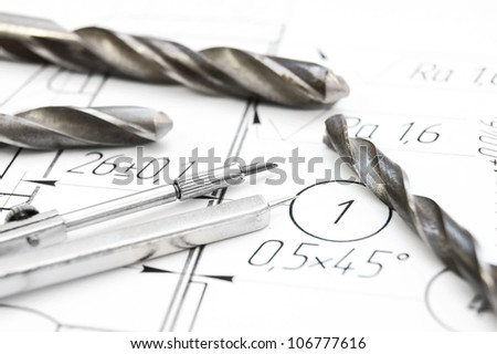 Compasses, drills on the drawing. - stock photo