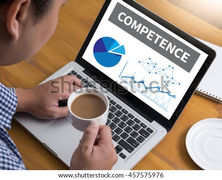 COMPETENCE  ( Skill Ability Proficiency Accomplishment) Businessman at work. Close-up top view of man working on laptop while sitting at the wooden desk , coffee - stock photo