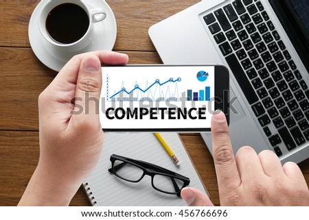 COMPETENCE  ( Skill Ability Proficiency Accomplishment) message on hand holding to touch a phone, top view, table computer coffee and book - stock photo