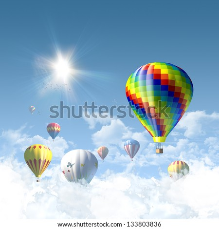 Competing hot-air balloons in sunny clear blue sky above clouds - great copy-space background for posters, cards or banners - stock photo