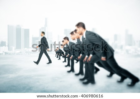 Competition concept with many businessmen about to run and one walking ahead of them on foggy city background - stock photo