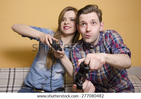 Competitive boyfriend and girlfriend playing video games, having fun. Selective focus on man  - stock photo