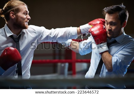 Competitive businessman giving his rival a facer - stock photo