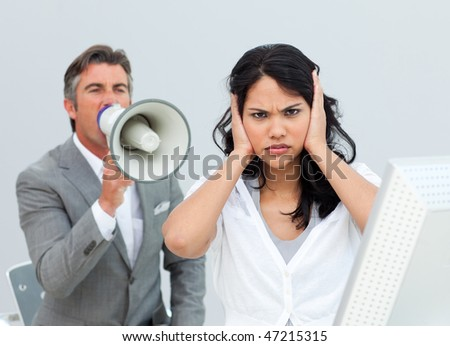 Competitive businessman shouting through a megaphone  in the office - stock photo