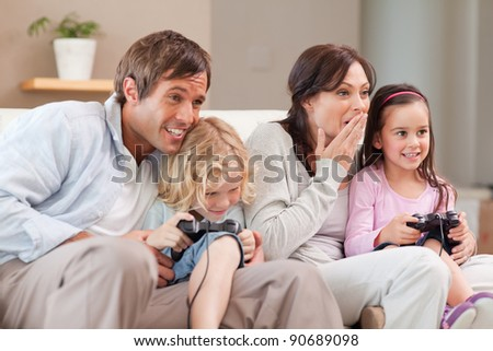 Competitive family playing video games in a living room - stock photo
