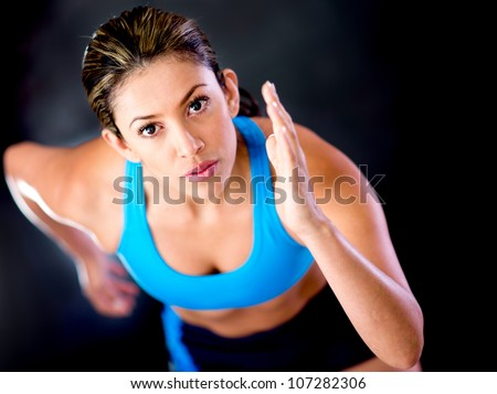 Competitive female runner over a dark background - stock photo