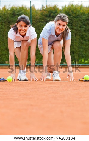 Competitive female tennis players racing at the court