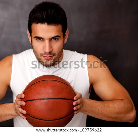 Competitive male basketball player holding the ball - stock photo