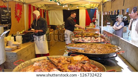 COMPIEGNE, FRANCE - MAY 22: Unidentified men cook and sell various meat snacks in a stall on a medieval market held during annual Joan of Arc festival on May 22, 2010 in Compiegne, France. - stock photo