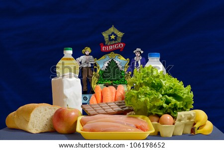 complete american state flag of maine covers whole frame, waved, crunched and very natural looking. In front plan are fundamental food ingredients for consumers, symbolizing consumerism - stock photo