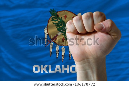 complete american state of oklahoma covers whole frame, waved, crunched and very natural looking. In front plan is clenched fist symbolizing determination - stock photo