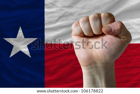 complete american state of texas covers whole frame, waved, crunched and very natural looking. In front plan is clenched fist symbolizing determination - stock photo