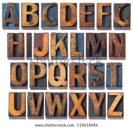 complete English alphabet - collage of 26 isolated vintage wood letterpress printing blocks, scratched and stained by blue, red and black ink - stock photo