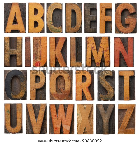 complete English alphabet - collage of 26 isolated vintage wood letterpress printing blocks, scratched and stained by ink patina - stock photo
