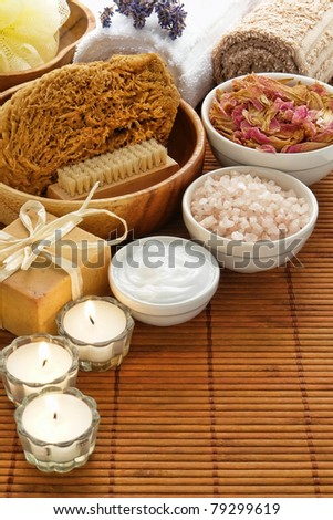 Complete experience kit of total body care accessories and cosmetics items for a pampering aromatherapy and wellness relaxation session in a spa with natural sponge, bath salts, facial cream, bar soap - stock photo