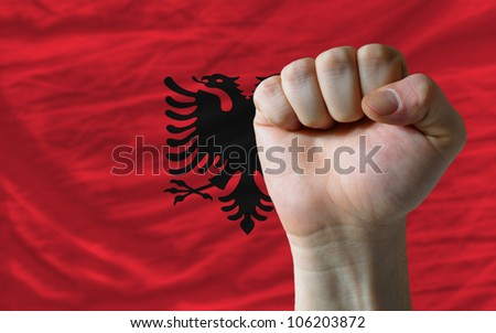 complete national flag of albania covers whole frame, waved, crunched and very natural looking. In front plan is clenched fist symbolizing determination - stock photo