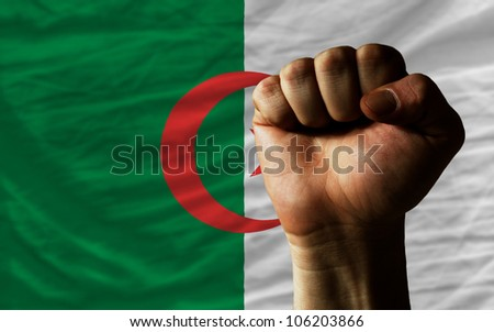 complete national flag of algeria covers whole frame, waved, crunched and very natural looking. In front plan is clenched fist symbolizing determination - stock photo