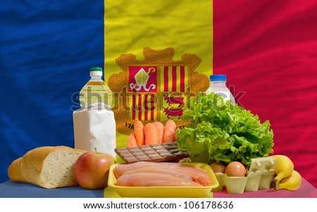 complete national flag of andorra covers whole frame, waved, crunched and very natural looking. In front plan are fundamental food ingredients for consumers, symbolizing consumerism - stock photo
