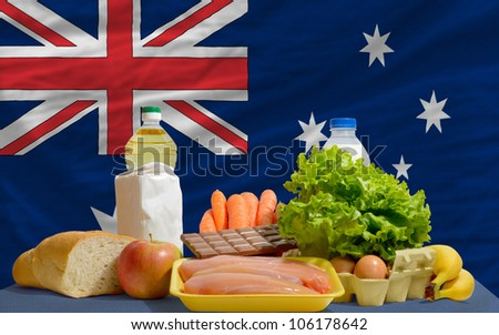 complete national flag of australia covers whole frame, waved, crunched and very natural looking. In front plan are fundamental food ingredients for consumers, symbolizing consumerism