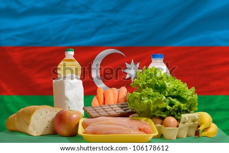 complete national flag of azerbaijan covers whole frame, waved, crunched and very natural looking. In front plan are fundamental food ingredients for consumers, symbolizing consumerism - stock photo