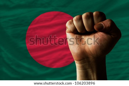 complete national flag of bangladesh covers whole frame, waved, crunched and very natural looking. In front plan is clenched fist symbolizing determination - stock photo