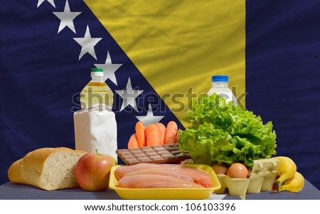 complete national flag of bosnia herzegovina covers whole frame, waved, crunched and very natural looking. In front plan are fundamental food ingredients for consumers, symbolizing consumerism - stock photo