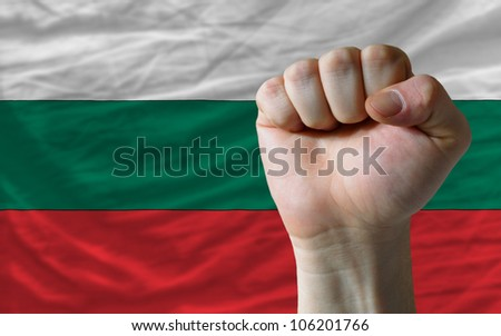 complete national flag of bulgaria covers whole frame, waved, crunched and very natural looking. In front plan is clenched fist symbolizing determination - stock photo