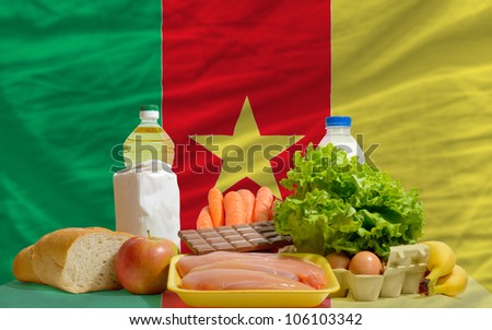 complete national flag of cameroon covers whole frame, waved, crunched and very natural looking. In front plan are fundamental food ingredients for consumers, symbolizing consumerism an human needs - stock photo