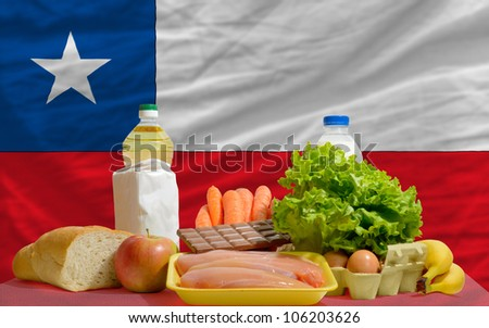 complete national flag of chile covers whole frame, waved, crunched and very natural looking. In front plan are fundamental food ingredients for consumers, symbolizing consumerism - stock photo