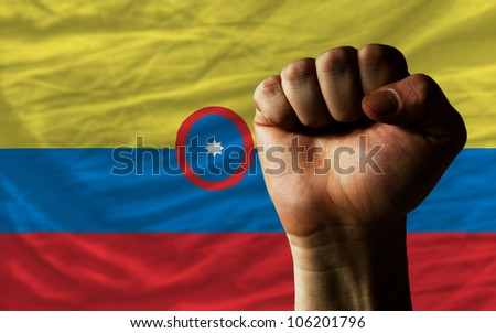complete national flag of colombia covers whole frame, waved, crunched and very natural looking. In front plan is clenched fist symbolizing determination - stock photo