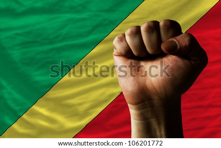 complete national flag of congo covers whole frame, waved, crunched and very natural looking. In front plan is clenched fist symbolizing determination - stock photo