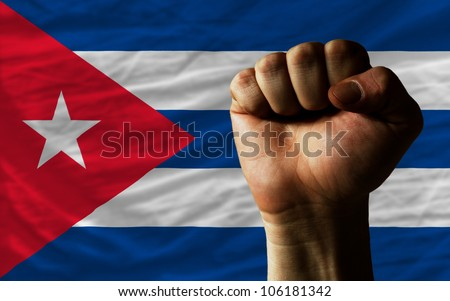 complete national flag of cuba covers whole frame, waved, crunched and very natural looking. In front plan is clenched fist symbolizing determination - stock photo