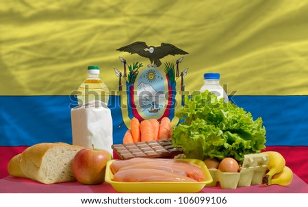 complete national flag of ecuador covers whole frame, waved, crunched and very natural looking. In front plan are fundamental food ingredients for consumers, symbolizing consumerism - stock photo