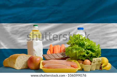 complete national flag of el salvador covers whole frame, waved, crunched and very natural looking. In front plan are fundamental food ingredients for consumers, symbolizing consumerism - stock photo