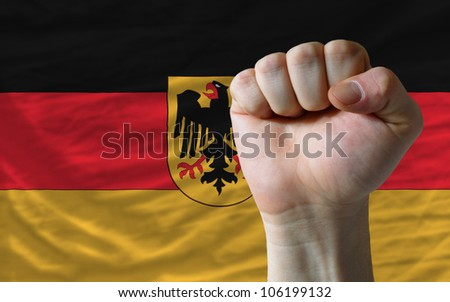 complete national flag of germany covers whole frame, waved, crunched and very natural looking. In front plan is clenched fist symbolizing determination - stock photo