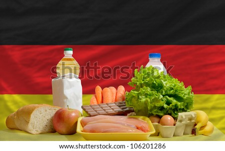 complete national flag of germany covers whole frame, waved, crunched and very natural looking. In front plan are fundamental food ingredients for consumers, symbolizing consumerism - stock photo