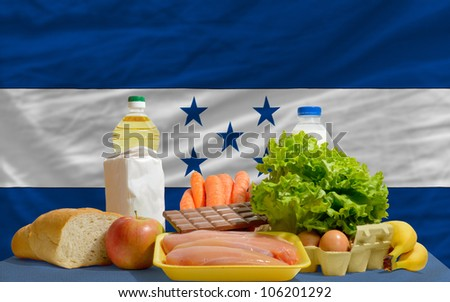 complete national flag of honduras covers whole frame, waved, crunched and very natural looking. In front plan are fundamental food ingredients for consumers, symbolizing consumerism - stock photo