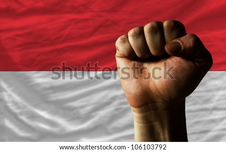complete national flag of indonesia covers whole frame, waved, crunched and very natural looking. In front plan is clenched fist symbolizing determination - stock photo