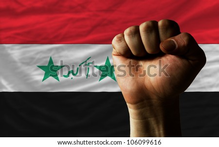 complete national flag of iraq covers whole frame, waved, crunched and very natural looking. In front plan is clenched fist symbolizing determination - stock photo