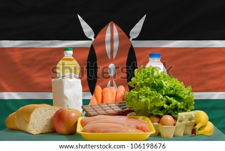 complete national flag of kenya covers whole frame, waved, crunched and very natural looking. In front plan are fundamental food ingredients for consumers, symbolizing consumerism - stock photo