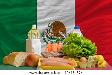 complete national flag of mexico covers whole frame, waved, crunched and very natural looking. In front plan are fundamental food ingredients for consumers, symbolizing consumerism - stock photo