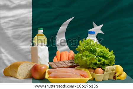 complete national flag of pakistan covers whole frame, waved, crunched and very natural looking. In front plan are fundamental food ingredients for consumers, symbolizing consumerism - stock photo