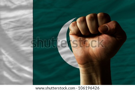 complete national flag of pakistan covers whole frame, waved, crunched and very natural looking. In front plan is clenched fist symbolizing determination - stock photo