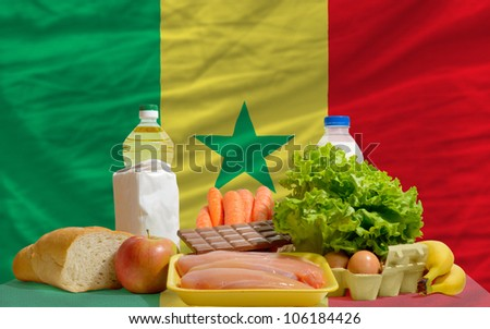 complete national flag of senegal covers whole frame, waved, crunched and very natural looking. In front plan are fundamental food ingredients for consumers, symbolizing consumerism - stock photo