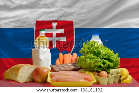 complete national flag of slovakia covers whole frame, waved, crunched and very natural looking. In front plan are fundamental food ingredients for consumers, symbolizing consumerism - stock photo