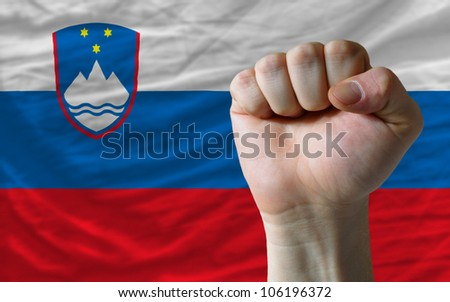 complete national flag of slovenia covers whole frame, waved, crunched and very natural looking. In front plan is clenched fist symbolizing determination - stock photo