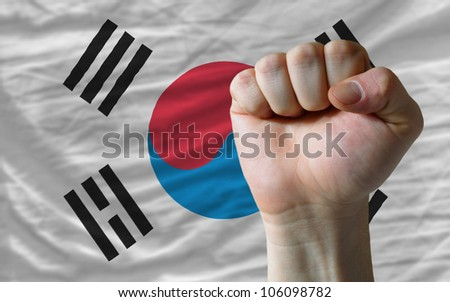 complete national flag of south korea covers whole frame, waved, crunched and very natural looking. In front plan is clenched fist symbolizing determination - stock photo