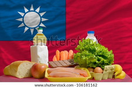 complete national flag of taiwan covers whole frame, waved, crunched and very natural looking. In front plan are fundamental food ingredients for consumers, symbolizing consumerism - stock photo