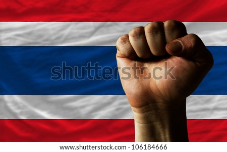 complete national flag of thailand covers whole frame, waved, crunched and very natural looking. In front plan is clenched fist symbolizing determination - stock photo