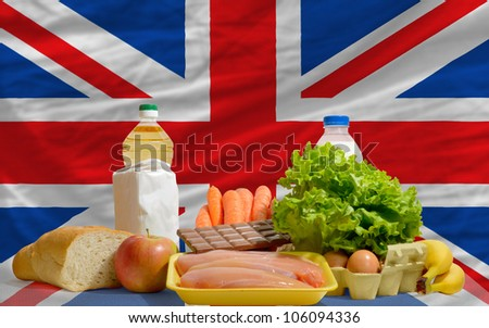 complete national flag of uk covers whole frame, waved, crunched and very natural looking. In front plan are fundamental food ingredients for consumers, symbolizing consumerism an human needs - stock photo